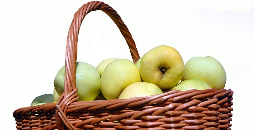 Basket with green apples in a garden on a white background